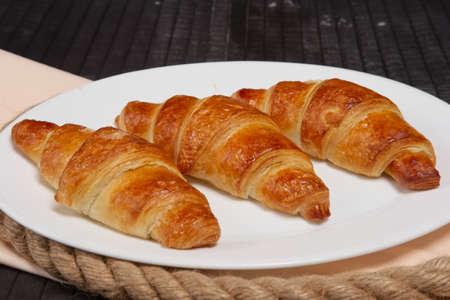 Fresh baked croissants on plate Imagens