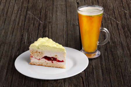 Cherry cake with whipped cream and glass of sea buckthorn tea on wooden table