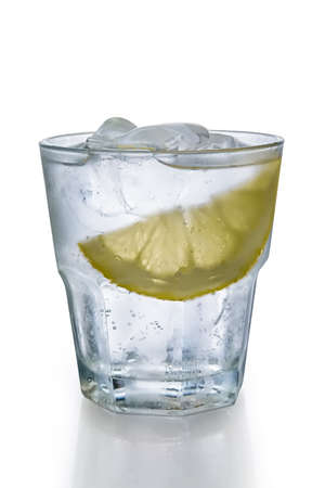 Misted glass of water with ice and slice of lemon