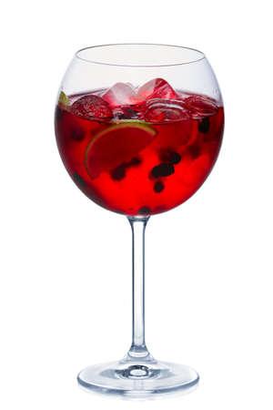 Cóctel de moras con vino espumoso, limón y cubitos de hielo en copa de vino redonda aislado en blanco
