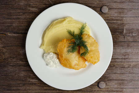 Top view of fish fillet in batter with mashed potato on wooden table