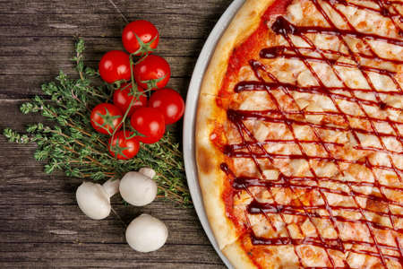 Pizza with barbecue sauce and ingredients on wooden table