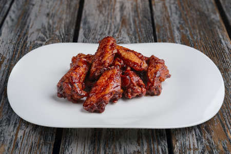 tasty grilled chicken wings Buffalo on a white dish on wooden table Zdjęcie Seryjne