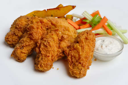 Buffalo chicken wings with fried potato and carrot and celery sticks