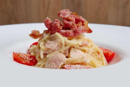 Teller mit Nudeln, serviert mit Speck und Schinken, dekoriert mit Tomaten-Kirsche Standard-Bild