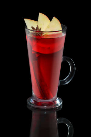 Cup of apple and cherry tea with cinnamon stick isolated on balck