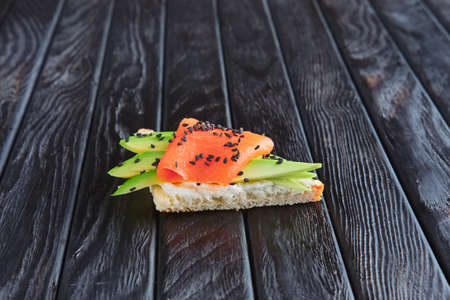 Appetizer for reception. Sandwich with smoked salmon, ricotta snd avocado Stock Photo