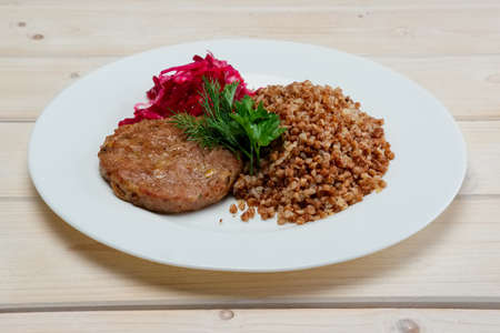 Portion of fried beef cutlet, boiled buckwheat and pickled red cabbage