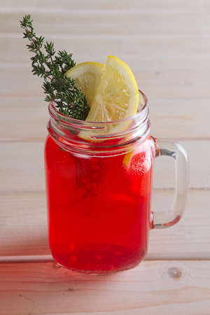 Cup of cranberry juice with citrus and rosemary