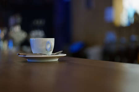 White cup of coffee with steam on wooden table near window