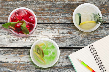 Top view of three glasses with cool lemonade on wooden table near notebook