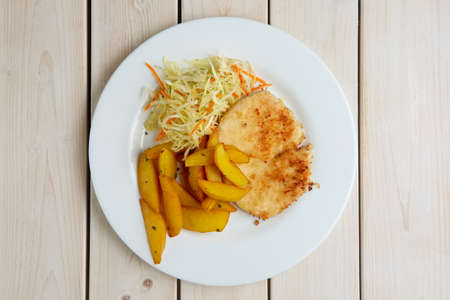 Chop cutlet with fried potato and fresh cabbage and carrot