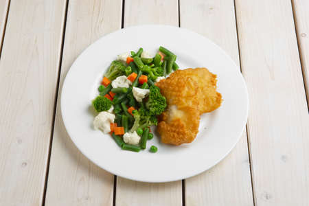 fish fillet in batter with boiled vegetables 写真素材