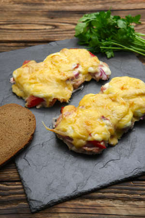 Baked in oven meat with mushrooms, tomato and cheese, servet on stone plate
