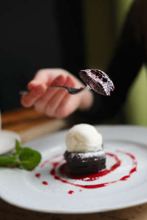 Shallow depth of foeld photo of brownie cake with ice-cream. Hand of girl with fork. 写真素材
