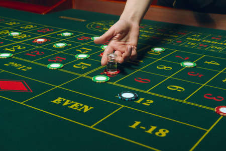 Casino pocker table with chips and cards. Winning combination. Hand of Croupier behind gambling table. Banque d'images