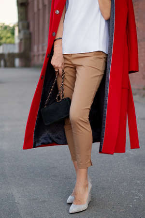 Long female legs in breeches and wool coat over the shoulders. Street style fashion.