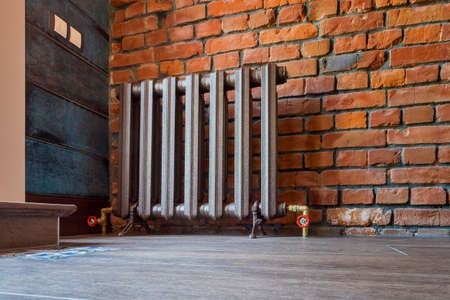 Vintage heating radiator for home with legs. Old cast iron central heating battery.