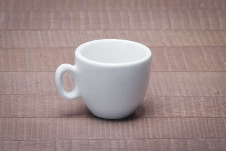 Clean and empty ceramic cup for espresso without saucer on wooden table. 免版税图像