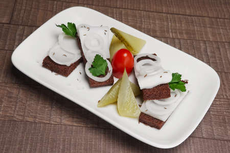 Traditional Russian appetizer to vodka: sandwich with lard and onion decorated with mild-cured cucumber and tomato.