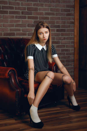 Sad girl acts and posing as a doll in old leather armchair.