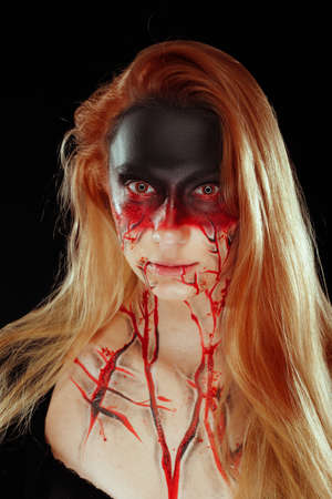 Mystic hero, bloody girl with blood on her face on a dark background. Fantasy horrible and Halloween makeup. Stok Fotoğraf