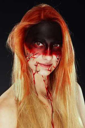 Mystic hero, bloody girl with blood on her face on a dark background. Fantasy horrible and Halloween makeup. Imagens