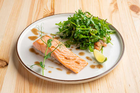 Steamed salmon with arugula and shrimps garnish