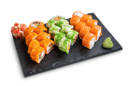 Big set of rolls with wasabi and pickled ginger on stone serving board isolated on white