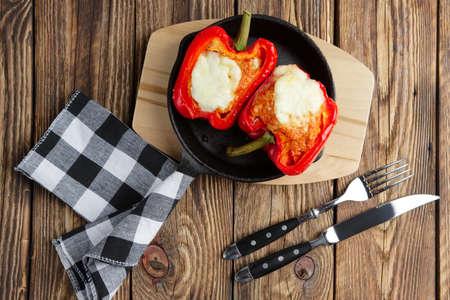 Mit Fleisch gefüllte Paprika mit geschmolzenem Käsemozzarella obenauf im Ofen in einer gusseisernen Pfanne gebacken. Ansicht von oben. Natürlicher hölzerner Hintergrund.