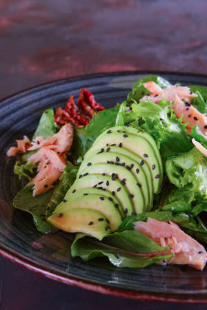 Closeup view of salad with salmon, avocado and sun dried tomatoes