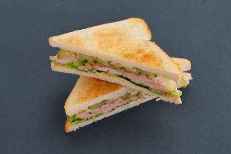 Club sandwich with soft cheese, ham, pickled cucumber and sauce bbq