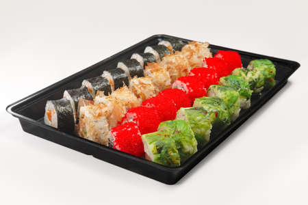 Plastic tray with set of rolls with smoked salmon, eel, chuka salad and flying fish roe on white background.