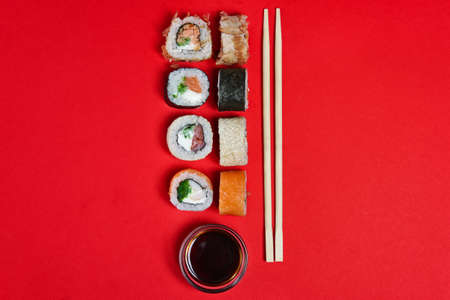 Set of salmon rolls, soy sauce and chopsticks on red background 免版税图像