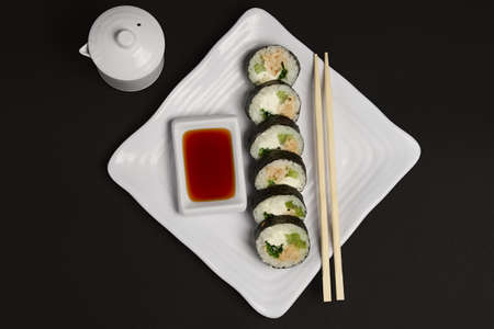 Top view of portion of chicken teriyaki rolls served on black paper with soy sauce and hashi.