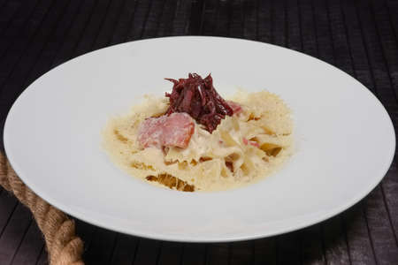 Big plate of pasta with ham, pickled onion and cheese