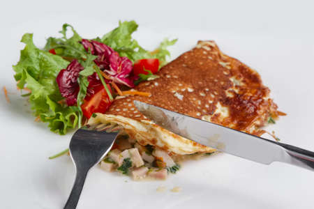 Cutting with knife omelet with ham and vegetables