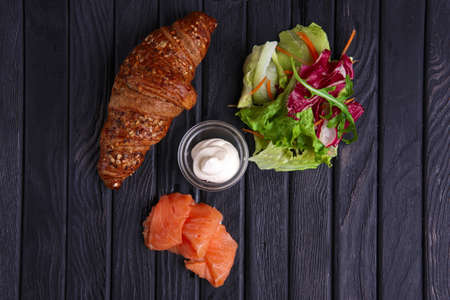 Croissant with salmon, salad and sour cream. Top view.
