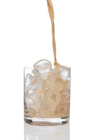 Irish creme liqueur pouring in a glass full of ice.