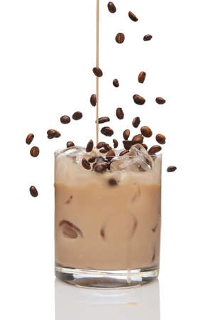 Coffee beans falling into cocktail and Irish creme liqueur pouring in a glass full of ice.