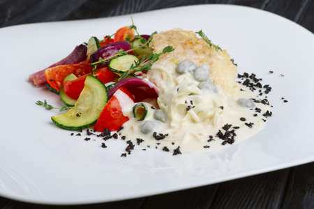 Fish fillet with grilled vegetables under cream sauce