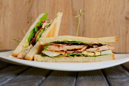 Placa con club sandwich en mesa de madera