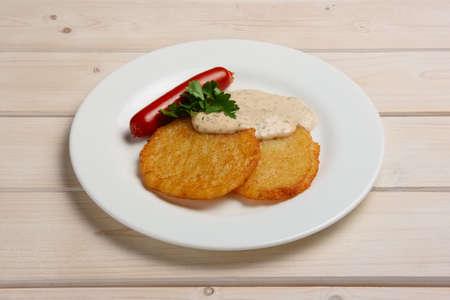 Portion of potato frlapjack with smoked sausage and mustard sauce Фото со стока