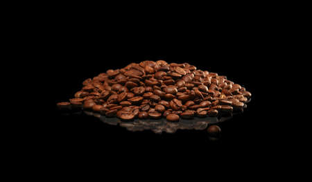 Heap of coffee beans on black