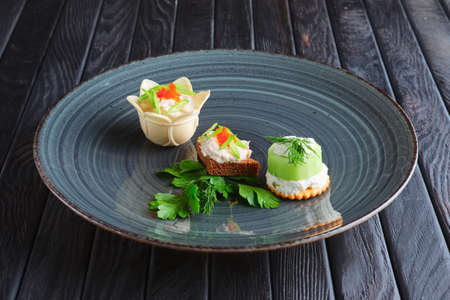Appetizer for reception. Set of tartlet with mozzarella and caviar, brown bread with fish pate and kiwi stuffed with cream cheese