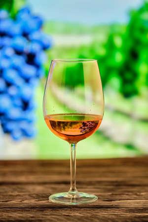 Kieliszek wina różanego z zamazaną winnicą na tle