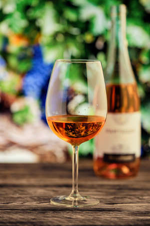 Glass of rose wine with blurred vineyard on background Фото со стока