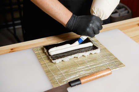Male hand making salmon rolls Stock Photo