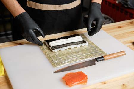 Male hand making salmon rolls Imagens