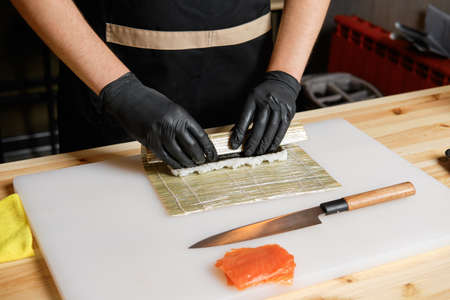 Male hand wrapping salmon rolls Imagens